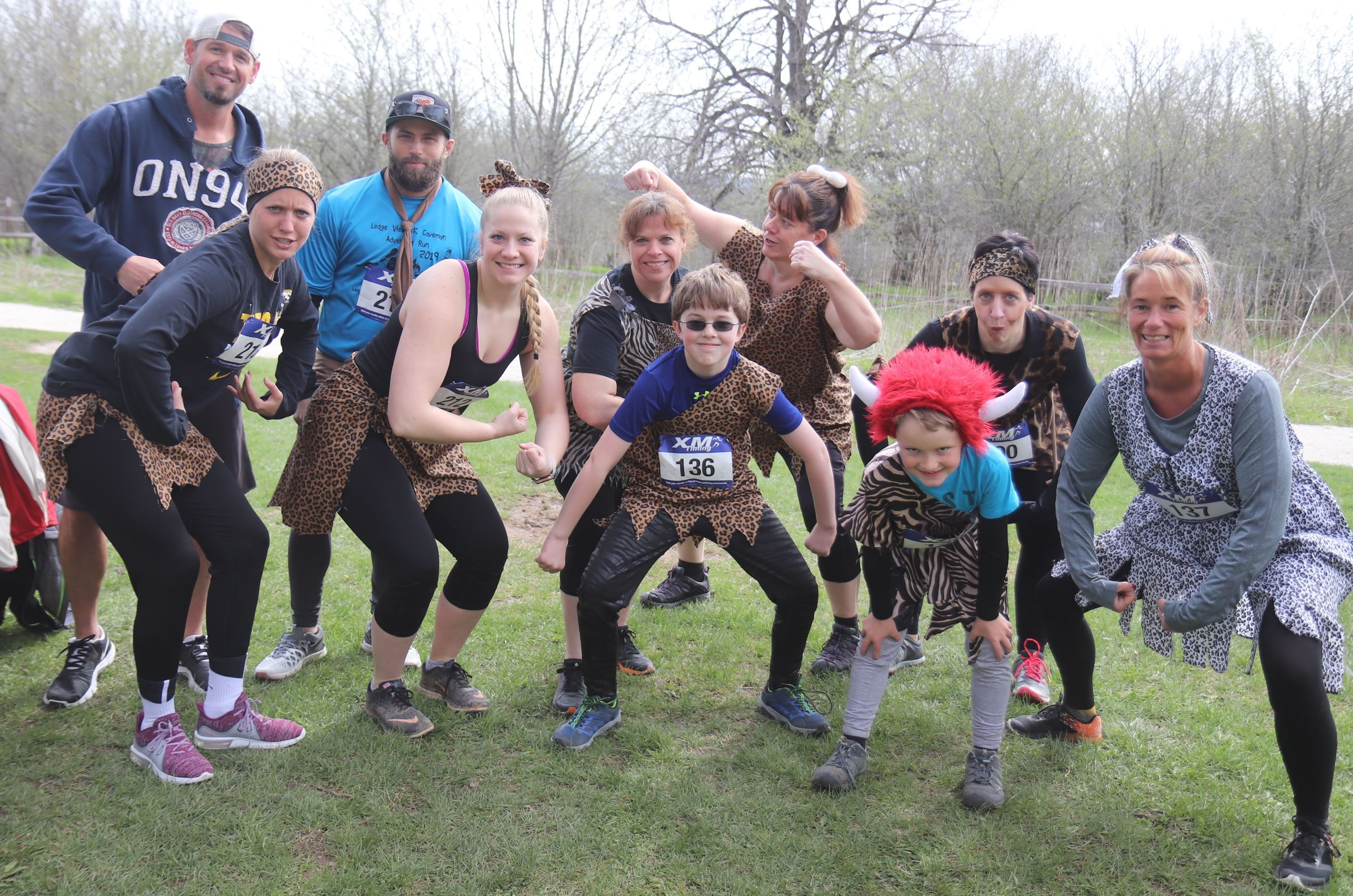 10 people posing in caveman costumes before a race