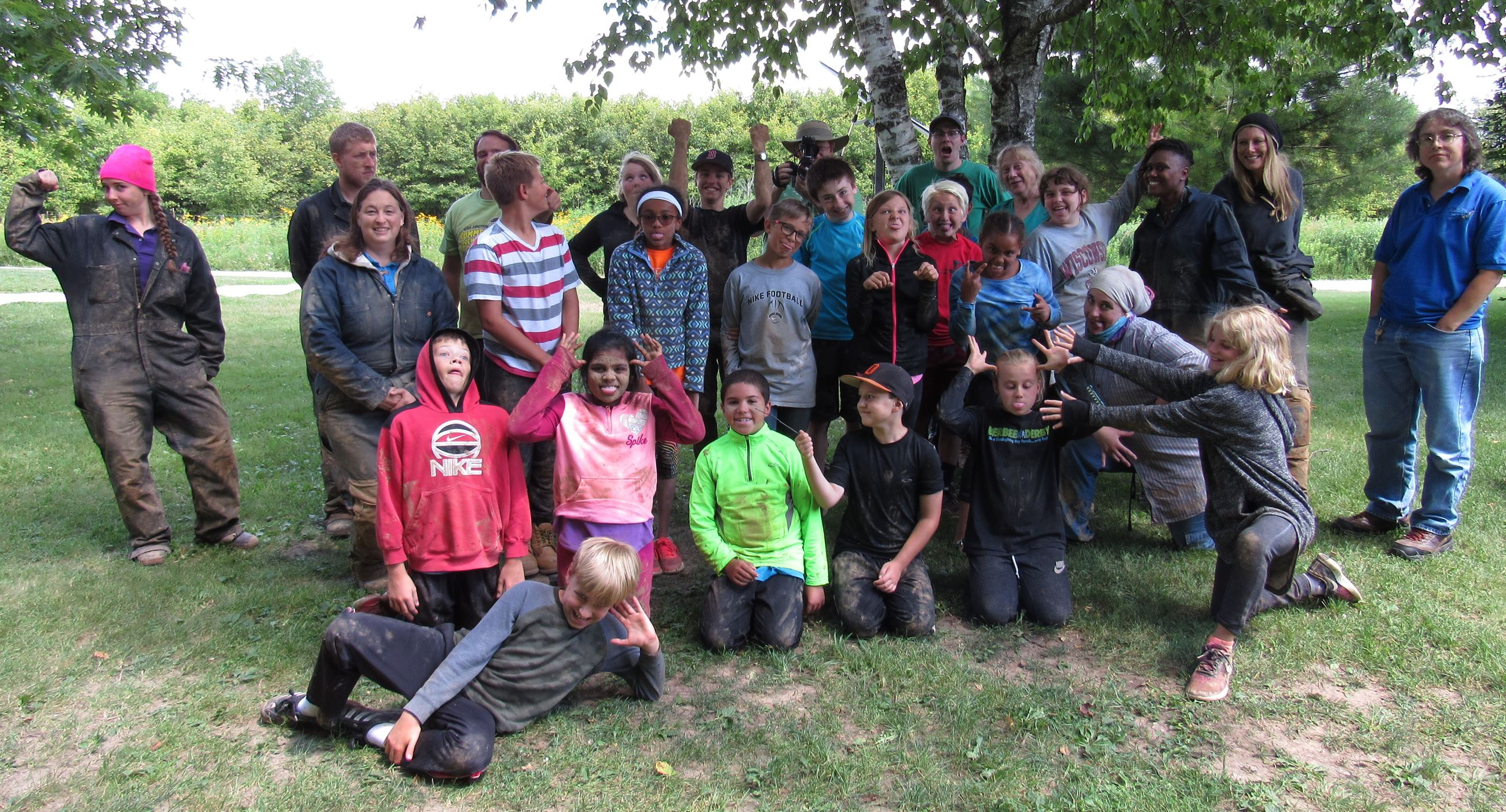 A group of muddy kids pulling funny faces. The kids just got back from caving.
