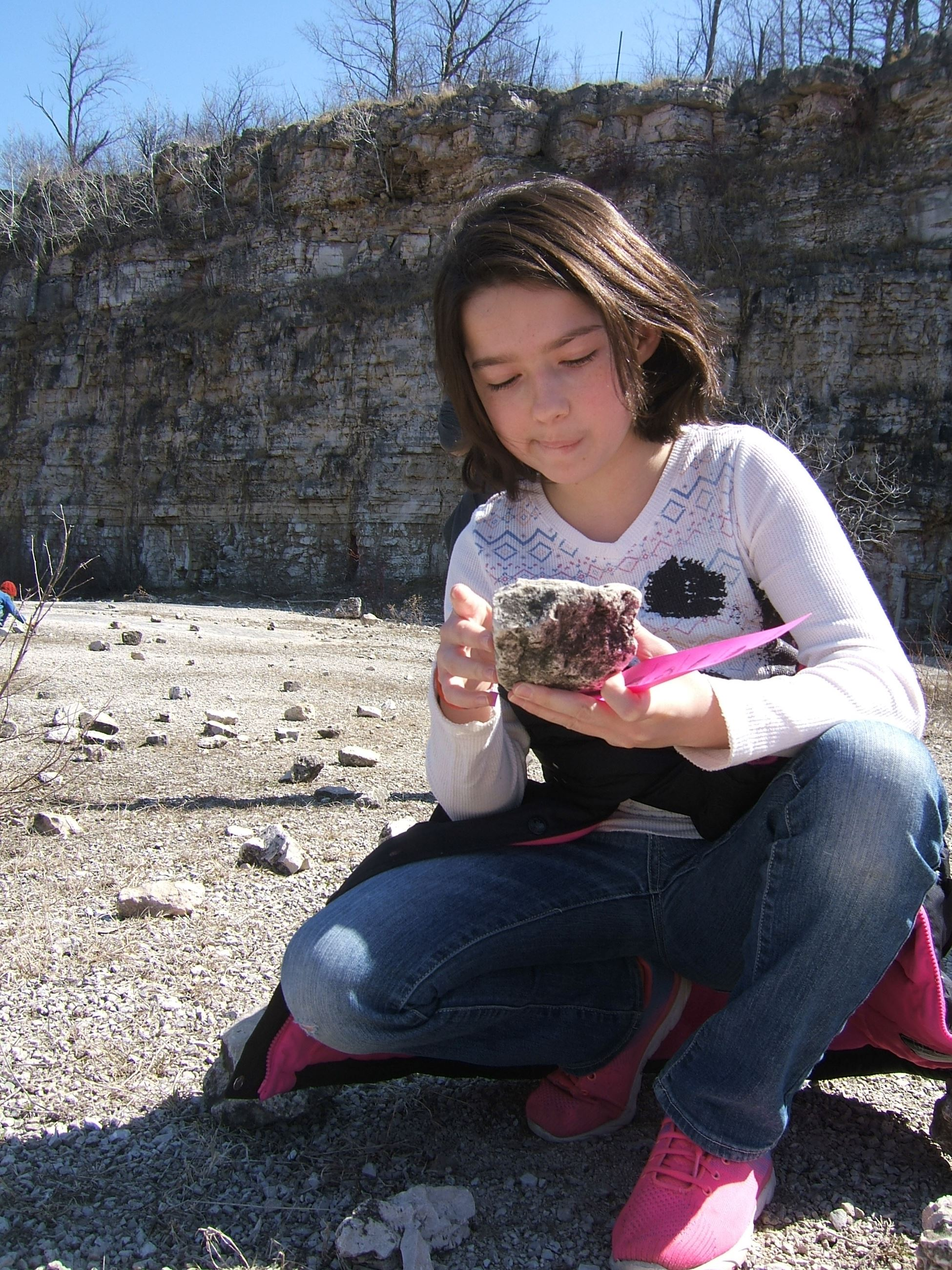 girl looking at a rock with a fossil in it