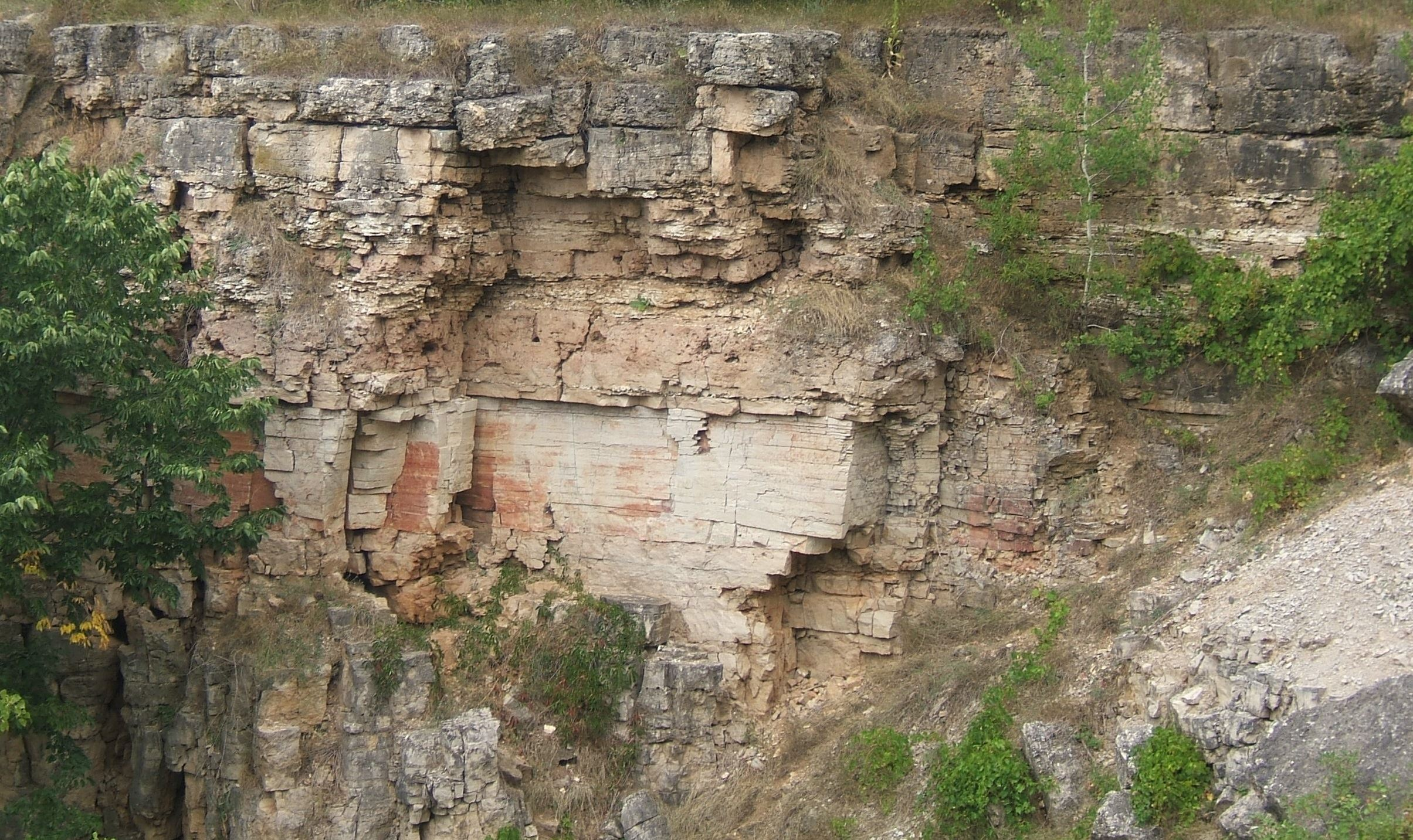 A cliff face showing cracks and eroded gravel