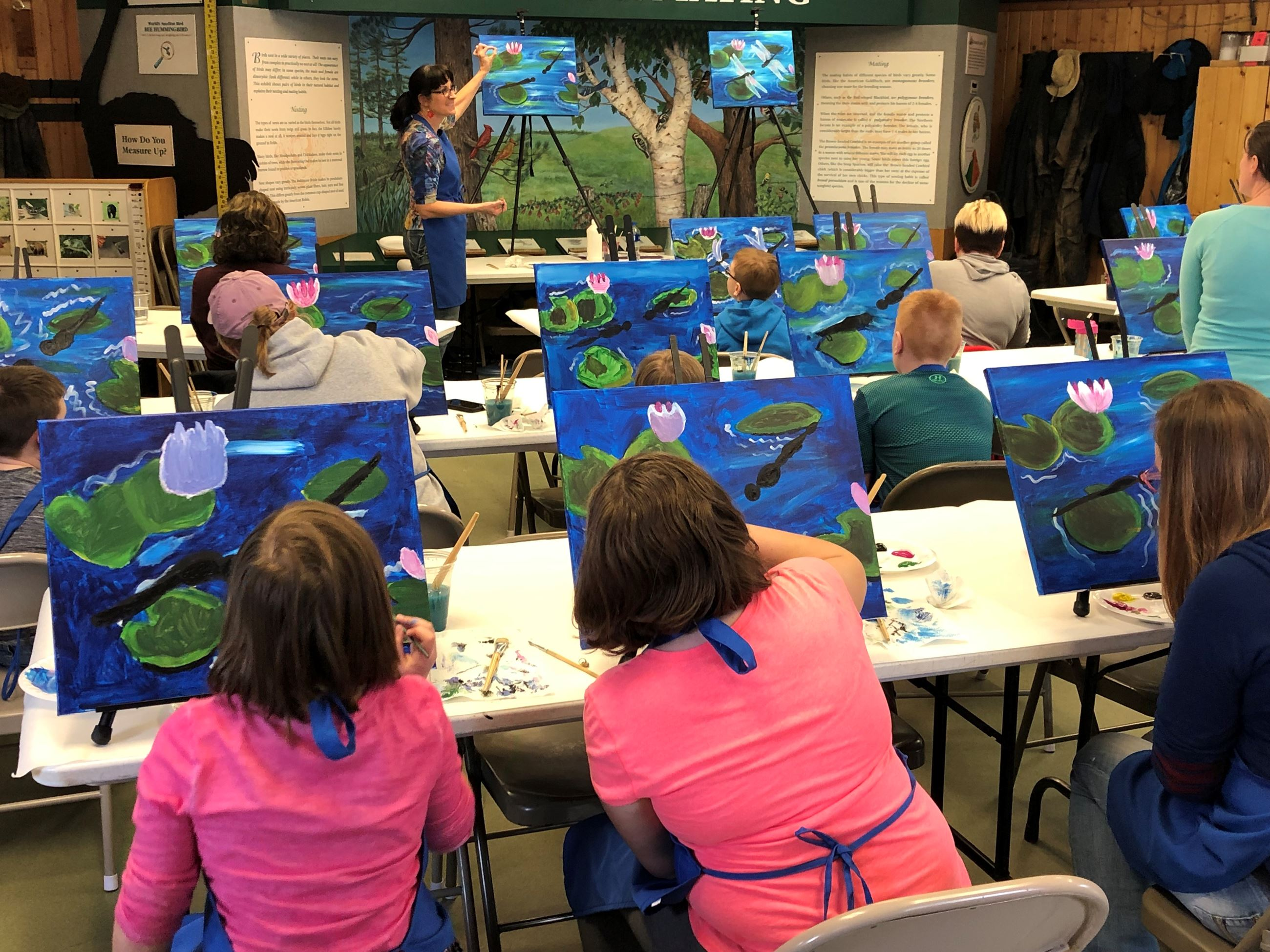 Ten people doing a guided painting class. The instructor is at the front of the room showing people