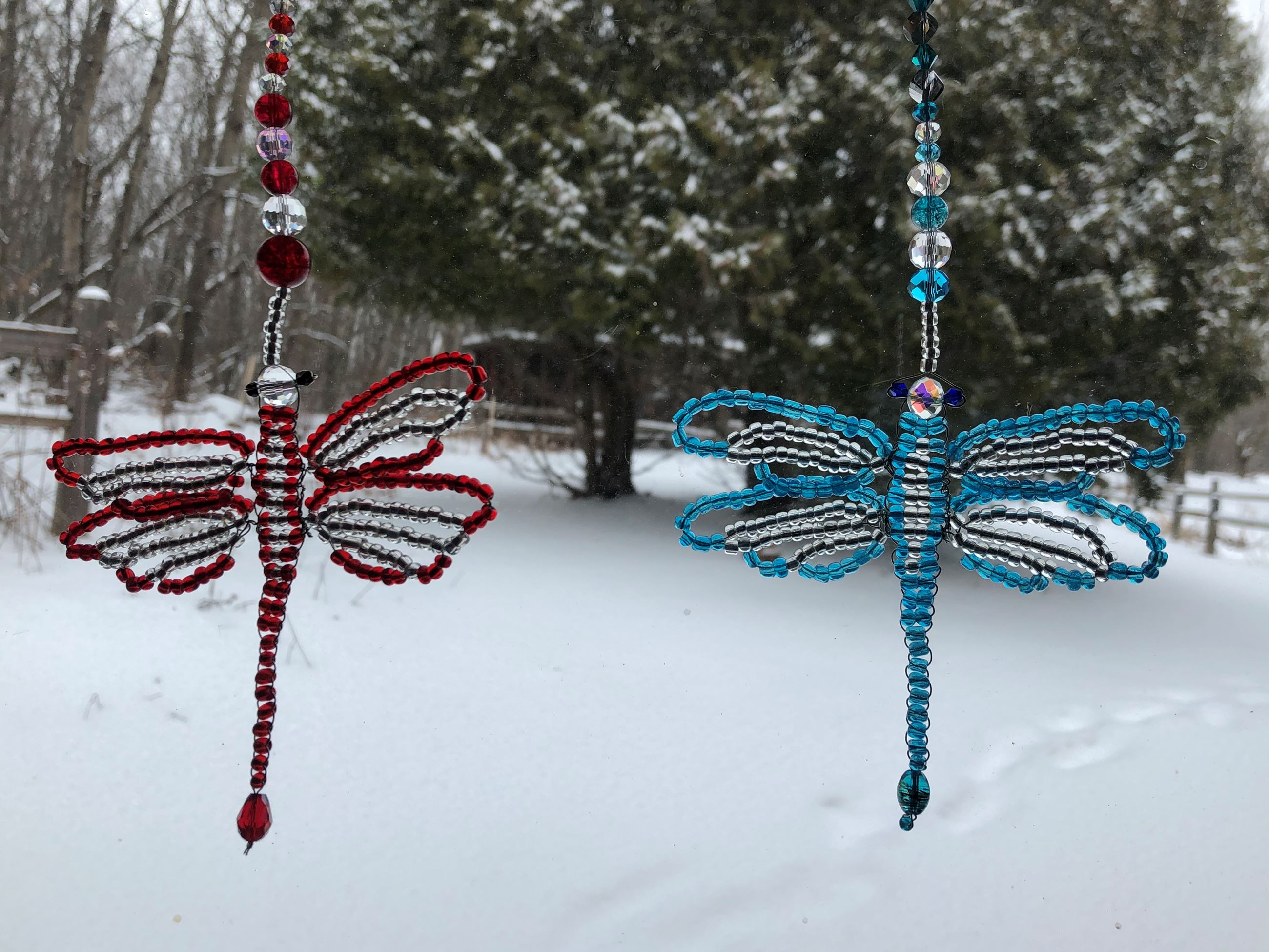 Two dragonfly sun catchers  made from beads. One is blue and the other is red and they are hanging i